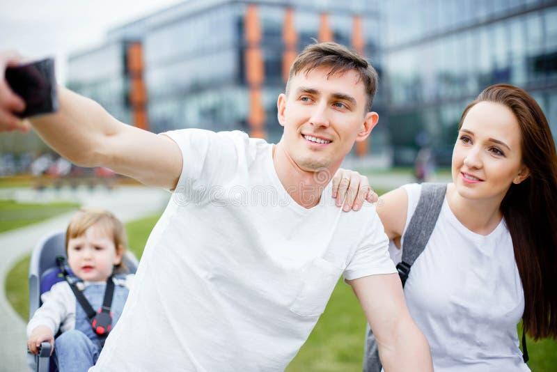Une famille heureuse fait le selfie sur un smartphone tout en marchant sur des bicyclettes pendant l'été images libres de droits