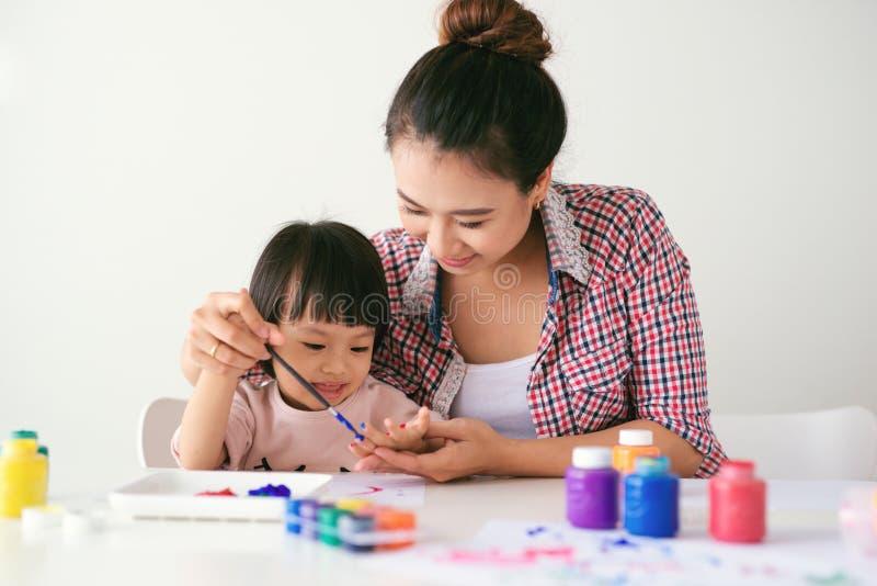 Une famille heureuse peint La maman aident son dessin de fille photos stock