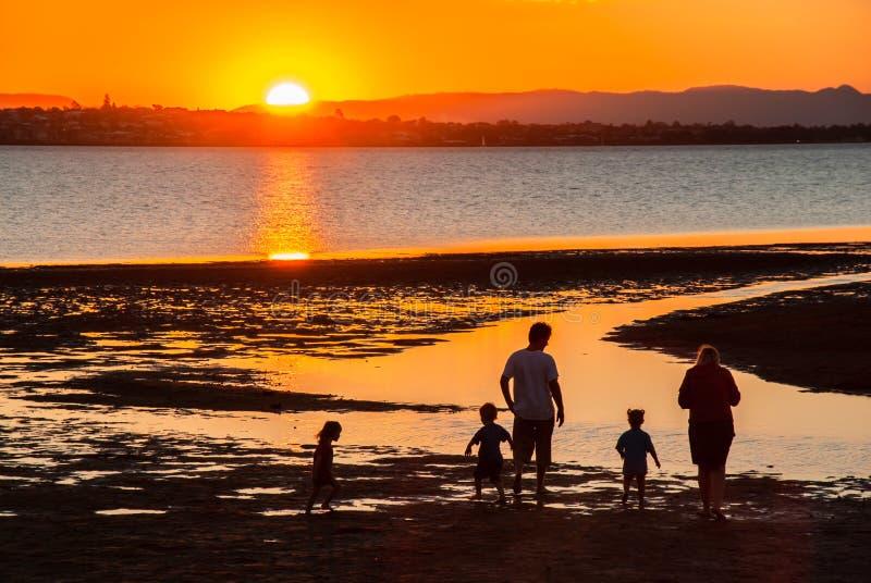 Une famille a plaisir à jouer sur la plage au coucher du soleil image libre de droits