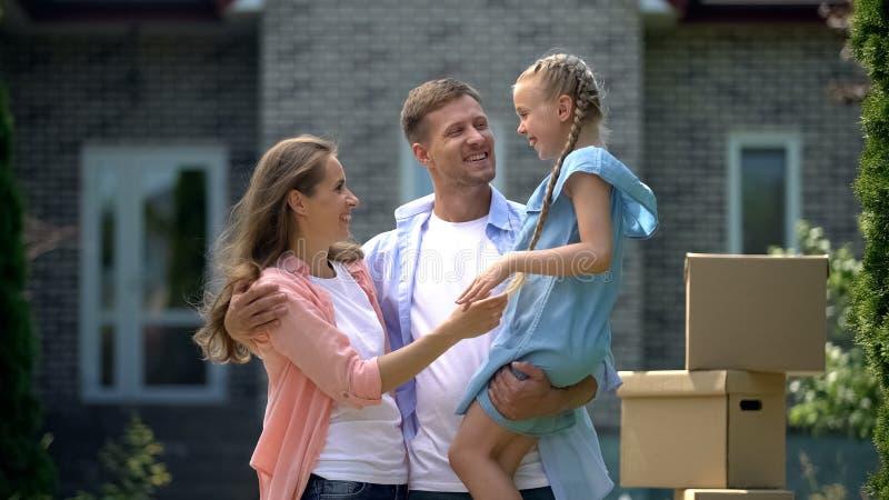 Une famille souriante en train de se faufiler, heureuse de déménager à la maison, prêt à taux d'intérêt bas images libres de droits