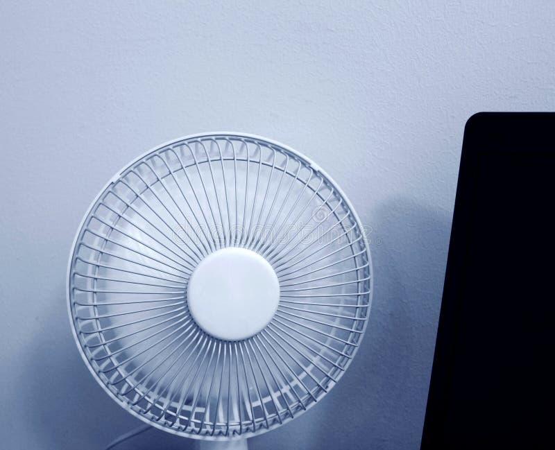 Une fan portative blanche dans les supports fonctionnants de mode à côté d'un ordinateur portable image libre de droits