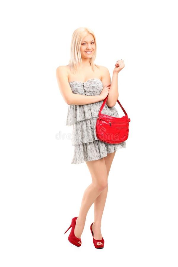 Une femelle blonde sexy attirante retenant un sac image libre de droits