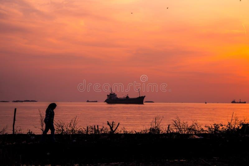 Une femelle marchant sur la côte de la mer avec un bateau dans l'eau au lever de soleil images stock