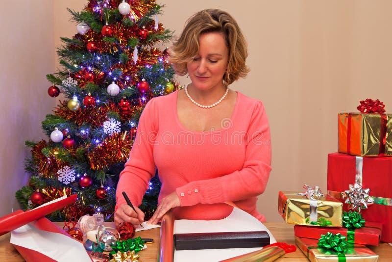Une femme à la maison enveloppant des cadeaux de Noël image stock