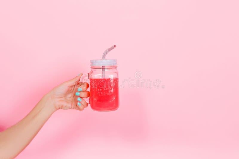 Une femme à la manucure turquoise branchée tient un verre transparent avec un savoureux soda brillant pour la fête d'anniversai images libres de droits