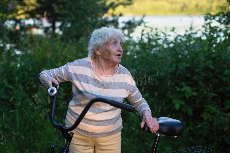 Une femme âgée à vélo et en plein air image libre de droits