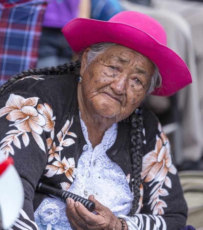 Une femme âgée est assise sur le trottoir et regarde la parade image libre de droits