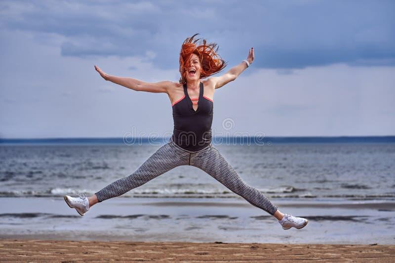 Une femme âgée moyenne avec les cheveux rouges fait avec émotion le saut image stock