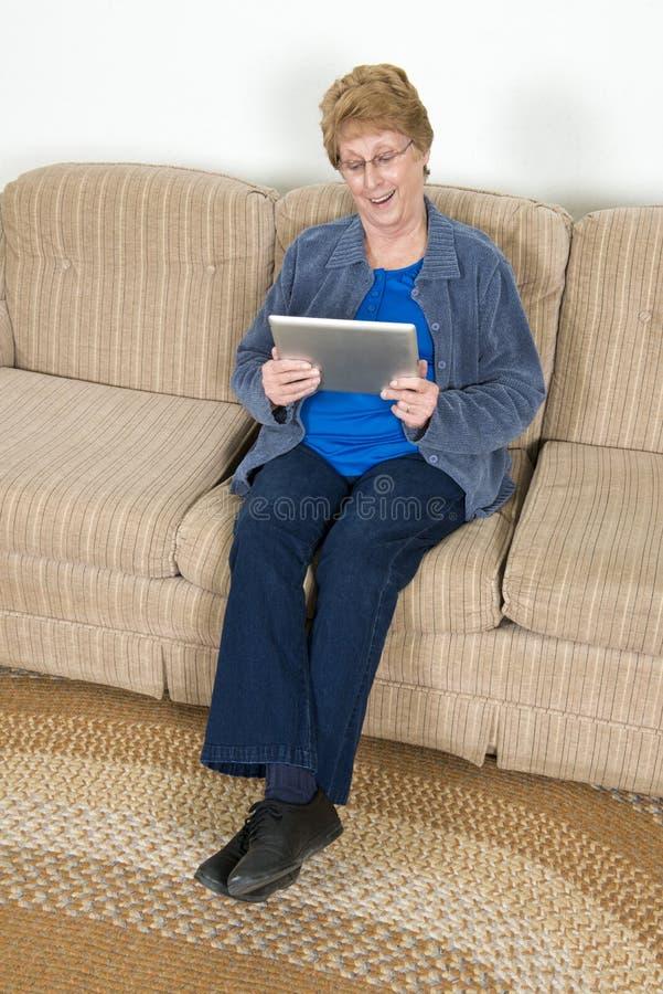 Ordinateur supérieur mûr d'Ipad d'utilisation de femme âgée photographie stock libre de droits