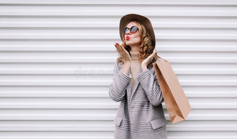 Une femme élégante avec un sac à provisions soufflant des lèvres rouges envoyant un baiser d'air doux portant un manteau gris, un image stock
