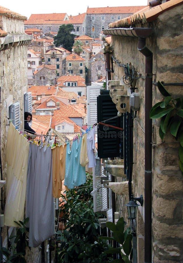 Une femme accrochant la blanchisserie sur une ligne entre deux maisons photographie stock libre de droits