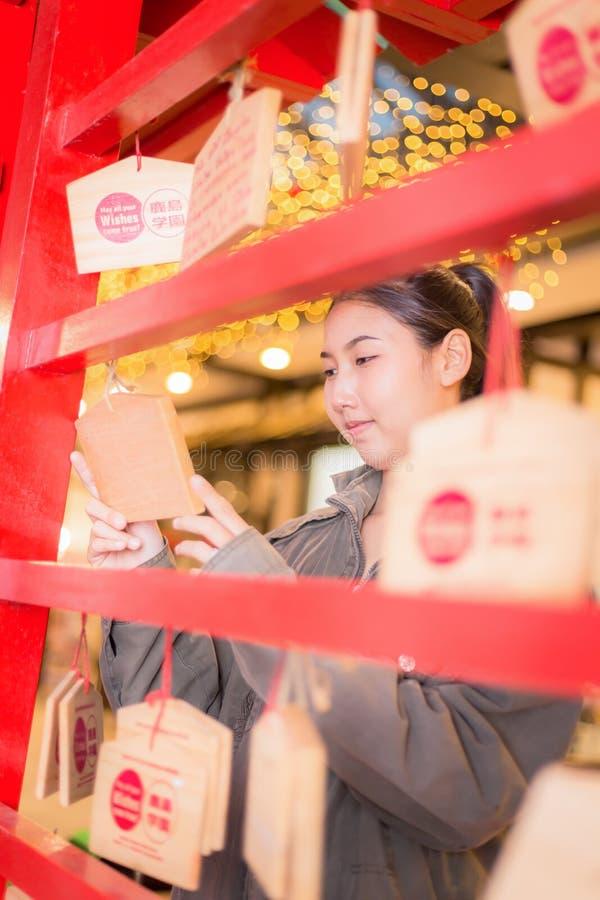 Une femme accrochant les souhaits dans le temple japonais images libres de droits
