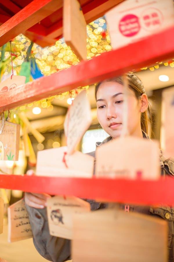 Une femme accrochant les souhaits dans le temple japonais photographie stock