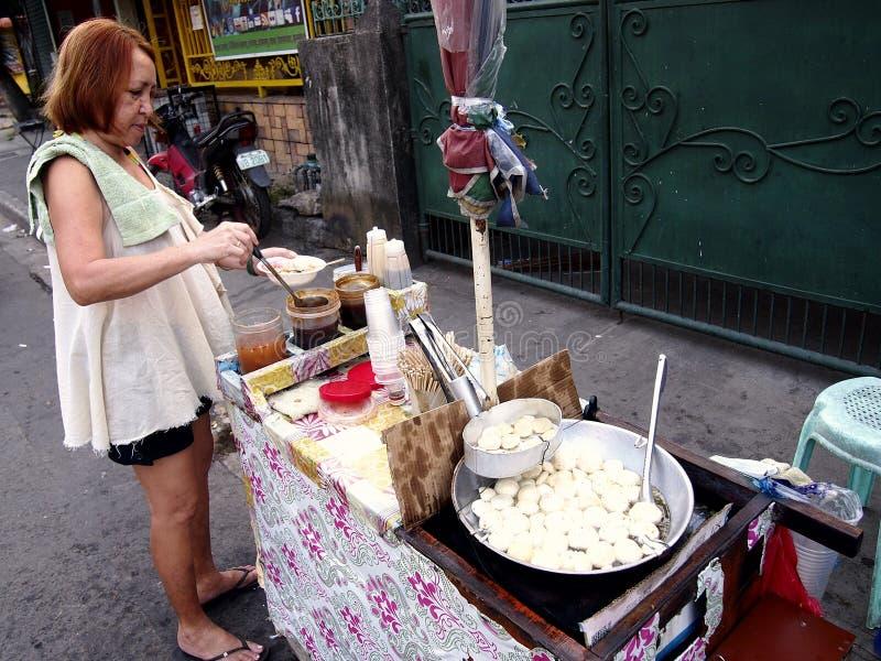 Une femme achète des fishballs d'un chariot le long d'une rue dans la ville d'Antipolo, Philippines photo libre de droits