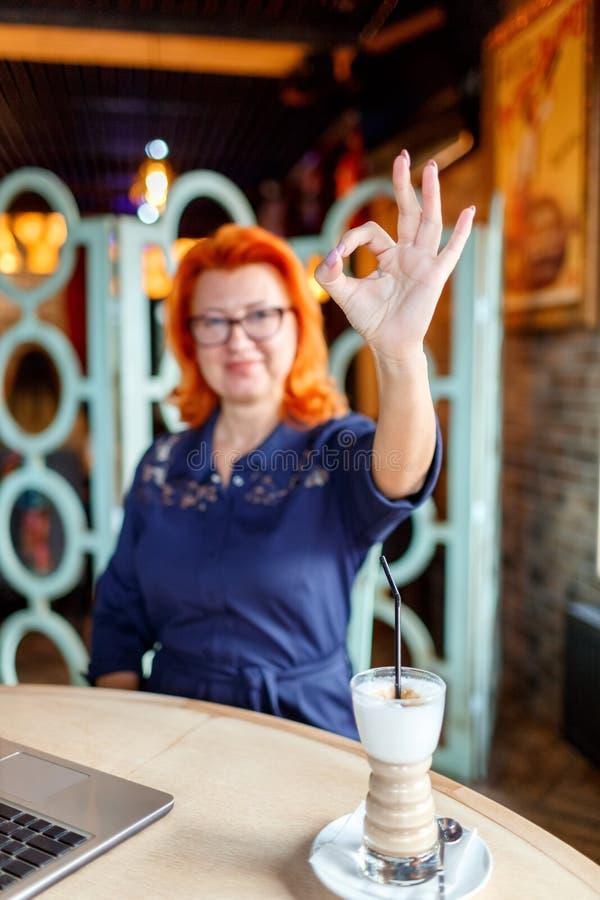 Une femme adulte en verres avec les cheveux rouges, s'assied un café et en montrant un ok de geste images stock