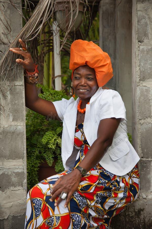 Une femme afro-am?ricaine joyeuse portant une robe nationale color?e lumineuse s'assied dans l'ouverture d'un belv?d?re de brique images stock