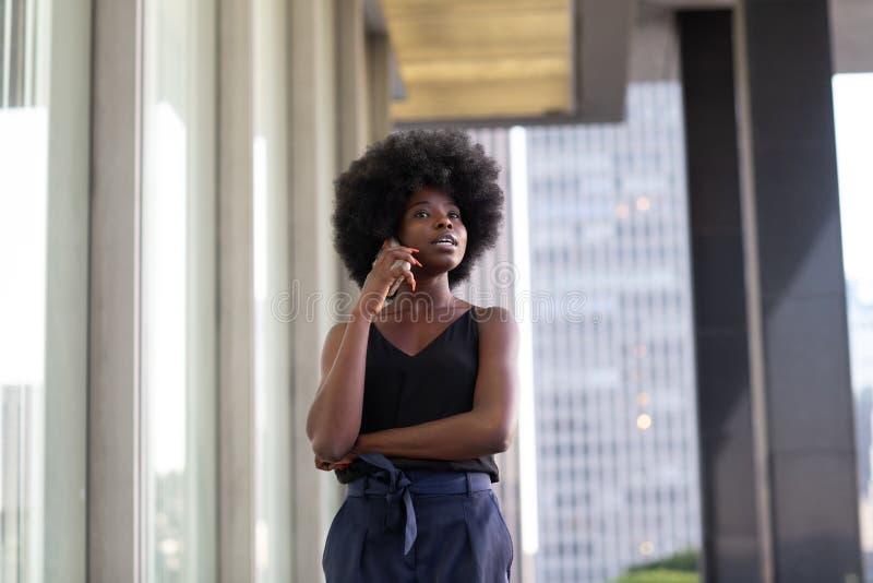 Une femme afro-américaine pensive parlant sur un téléphone portable, gratte-ciel de la ville en arrière-plan images stock
