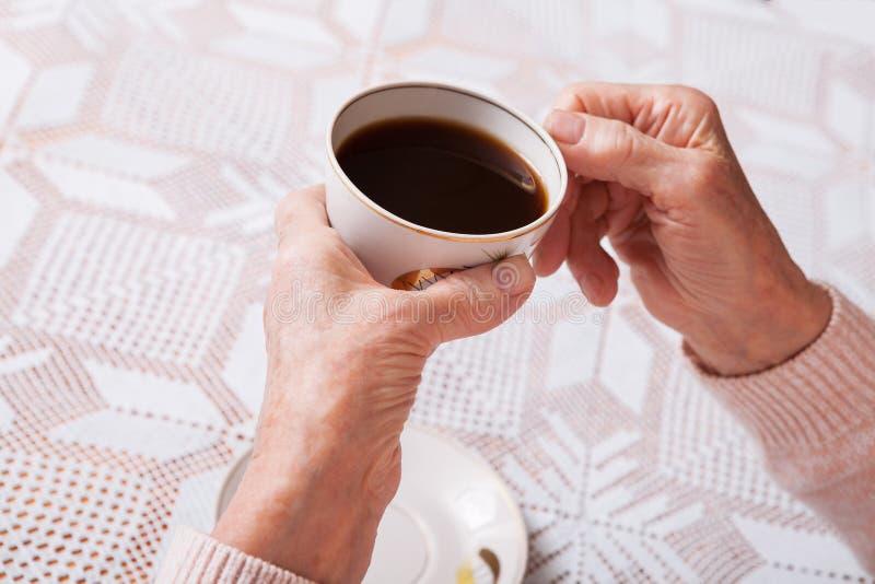 Une femme agée boit du thé à la maison Femme supérieure tenant la tasse de thé dans leurs mains au plan rapproché de table Horizo photographie stock