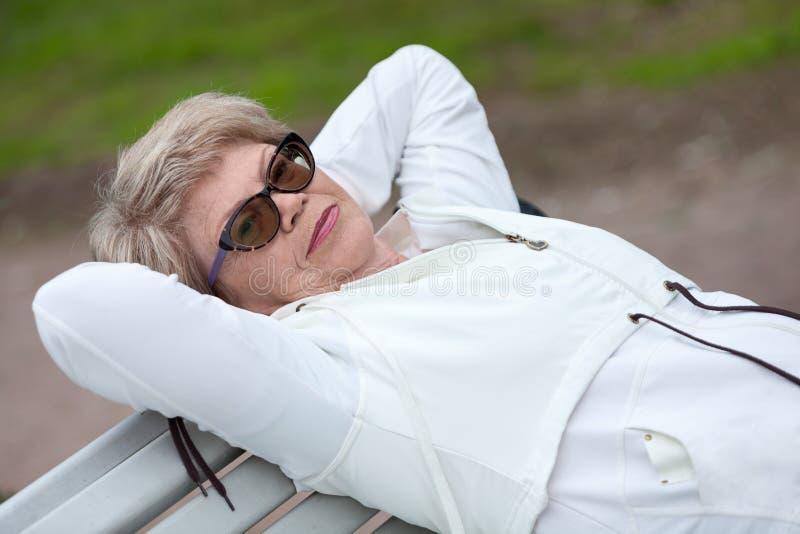 Une femme agée en verres se repose sur elle de retour, sur un banc photo libre de droits