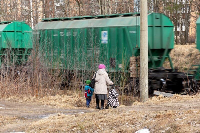 Une femme agée et un petit enfant attendent un train de fret photo libre de droits