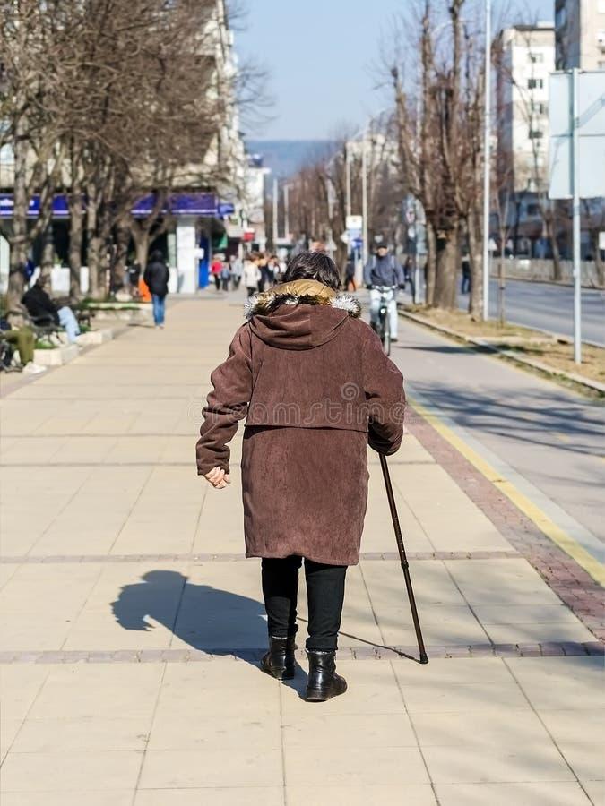 Une femme agée a habillé une veste brune et avec une canne dans sa main marchant le long d'une rue de ville un jour ensoleillé, v photographie stock libre de droits