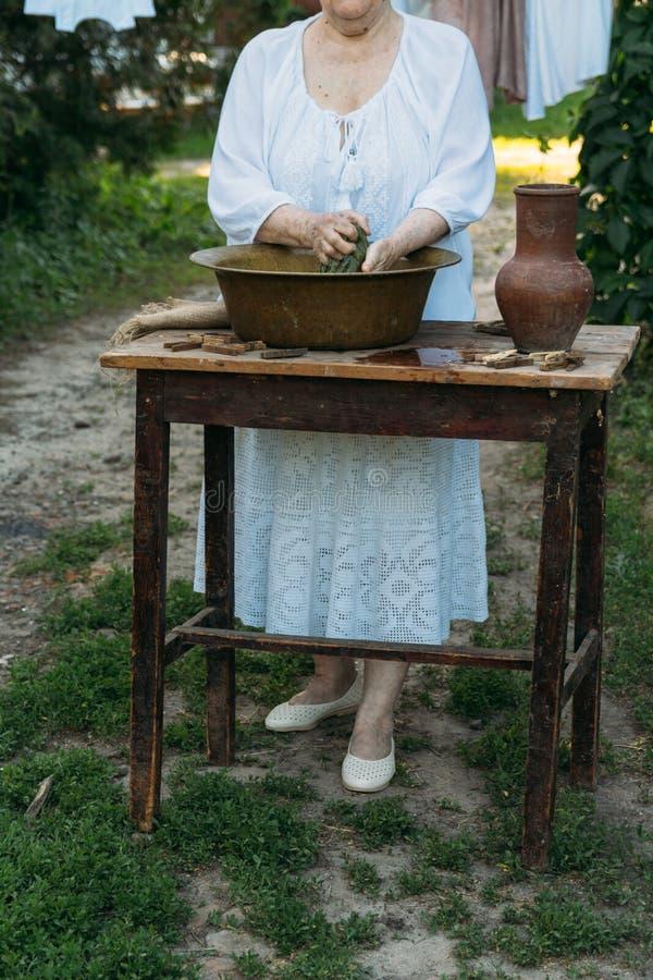 Une femme agée lave des vêtements dans le jardin dans l'habillement blanc de vintage Durée de pays les vêtements sèche sur une co images libres de droits