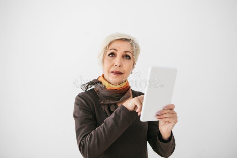 Une femme agée moderne positive tient un comprimé dans des ses mains et l'emploie La génération plus ancienne et la technologie m photos stock