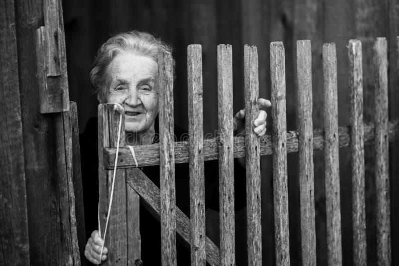 Une femme agée se tient derrière une barrière en bois dans le village photographie stock