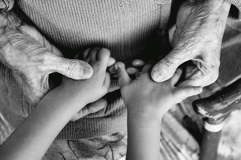 Une femme agée tenant les mains du ` s d'enfants, une canne en bois sur la rue arrière grand-mère et arrière-petit-fils Phot noir photographie stock