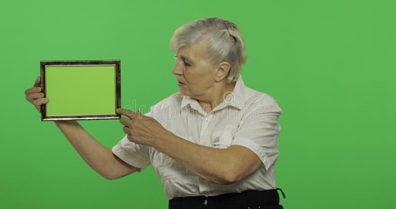 Une femme agée tenant un cadre avec l'image verte Vieux grand-m?re Plan rapproch? photos stock