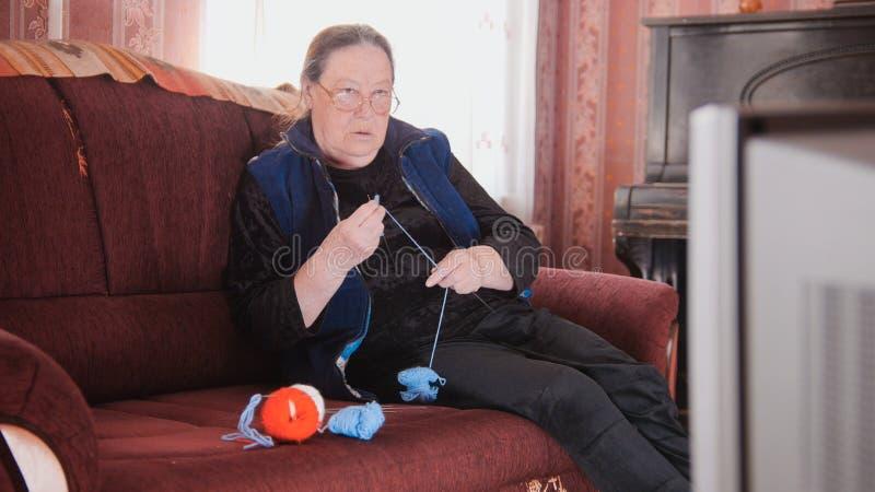 Une femme agée tricote des certaines chaussettes et TV de observation photo stock