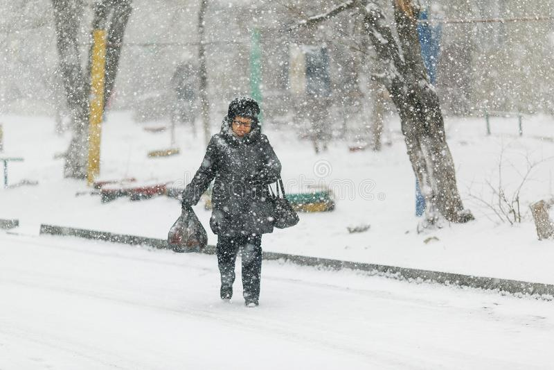 Une femme ag?e marche dans la neige sur le trottoir, se penchant sur une canne photographie stock libre de droits
