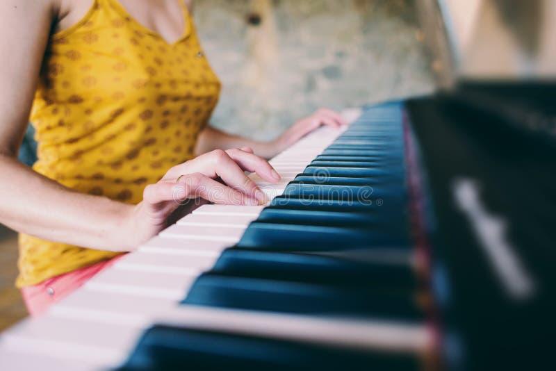 Une femme apprend à jouer le piano photo libre de droits