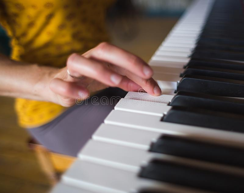 Une femme apprend à jouer le piano photos stock