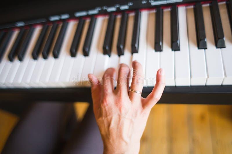 Une femme apprend à jouer le piano image libre de droits