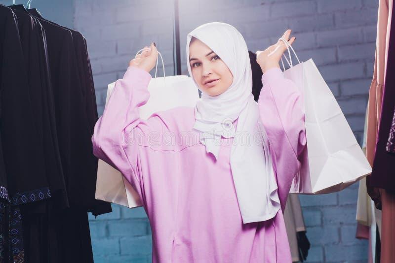 Une femme arabe en vêtements traditionnels musulmans achète une nouvelle robe dans un magasin oriental photo stock