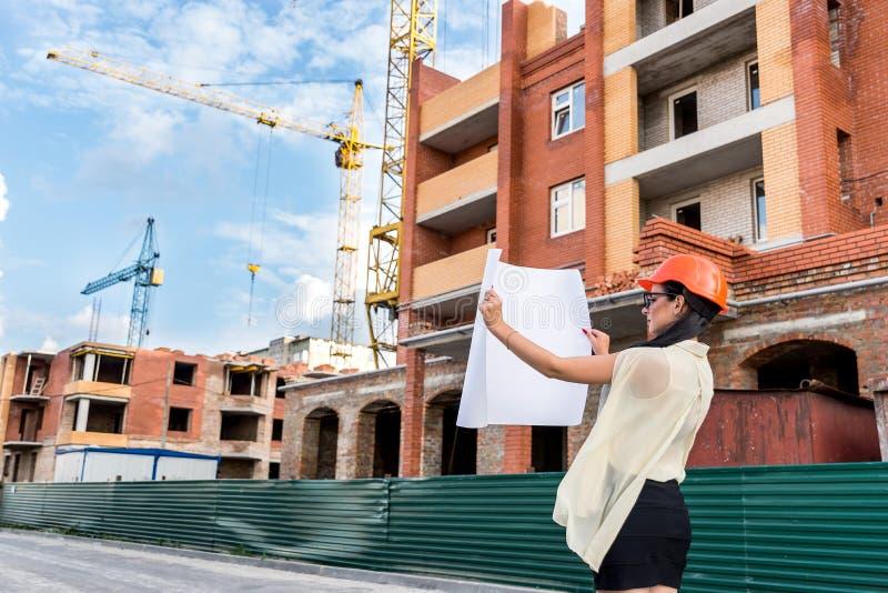 Une femme architecte au casque orange avec dessin près du chantier photos libres de droits