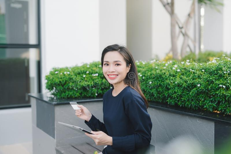 Une femme asiatique assez jeune d'affaires sur l'immeuble de bureaux ext?rieur de banc image stock
