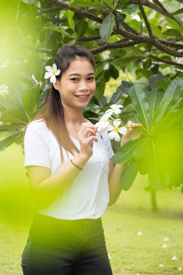 Une femme asiatique en T-shirt blanc avec plumeria sur les cheveux, Belle fille photographie stock