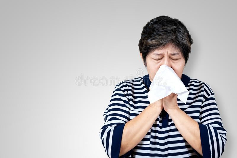 Une femme asiatique plus âgée a la grippe et éternue du problème saisonnier de virus de maladie photos stock