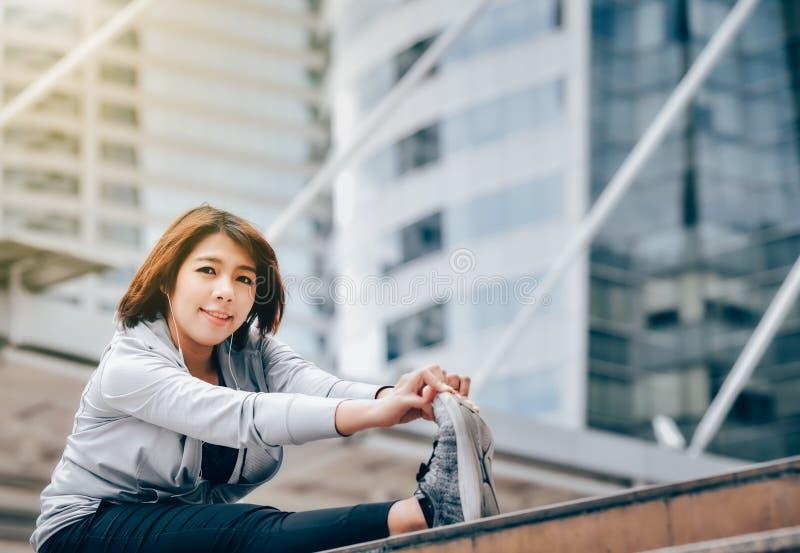 Une femme asiatique se chauffe pour s'exercer dans une grande ville guérissez photographie stock