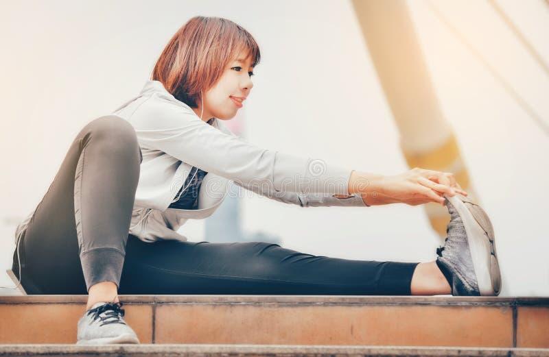 Une femme asiatique se chauffe pour s'exercer dans une grande ville guérissez photos libres de droits