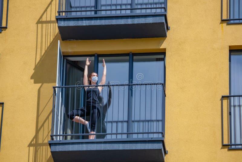 Une femme au masque pratique le yoga sur le balcon photo libre de droits