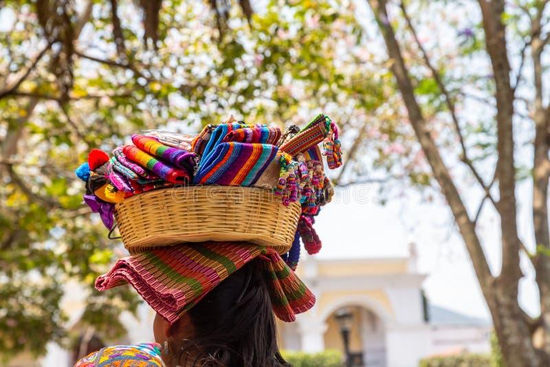 Une femme avec une corbeille de soevenirs sur la tête dans la ville d'Antigua au Guatemala photo libre de droits