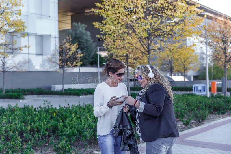 Une femme avec des écouteurs dit quelque chose à l'autre au sujet de quelque chose qu'elle voit à un téléphone portable images libres de droits