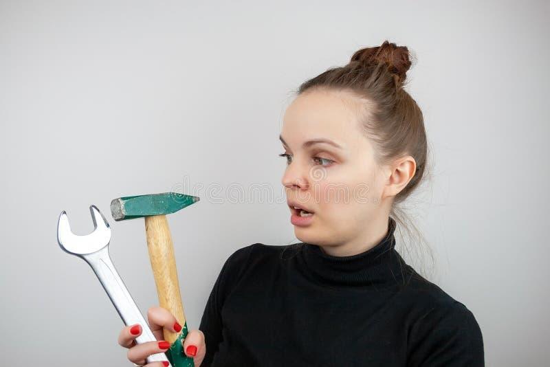 Une femme avec des cheveux liés et un chandail noir regarde étonnée un marteau et une grande clé, tout en hoding les dans des ses photographie stock libre de droits