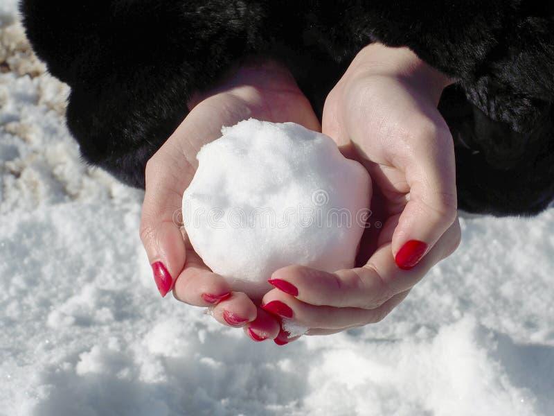 Une femme avec des ongles manucurés d'une écarlate fait à un snowballon un chemin couvert de neige photos libres de droits