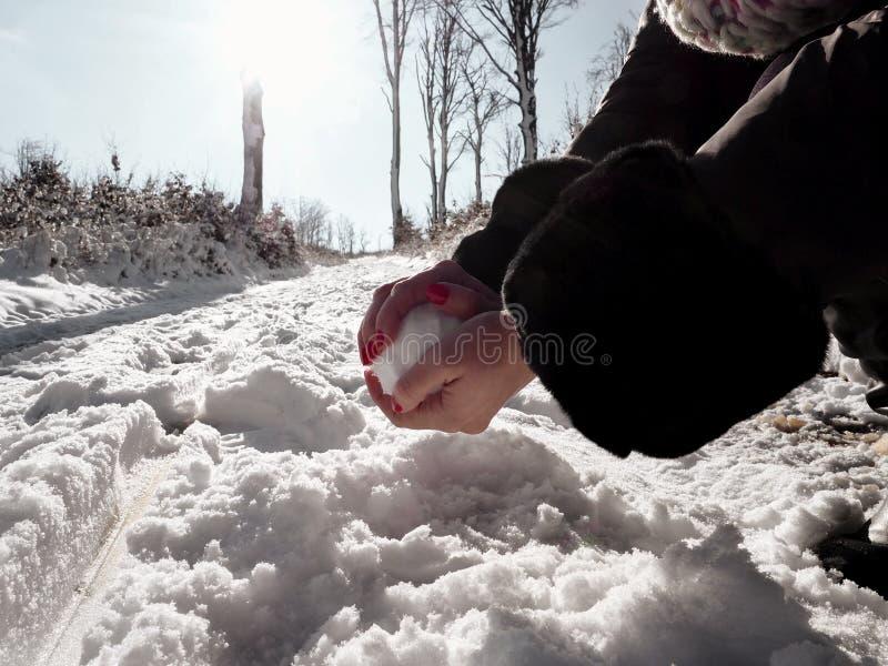Une femme avec des ongles manucurés d'une écarlate fait à un snowballon un chemin couvert de neige photo stock