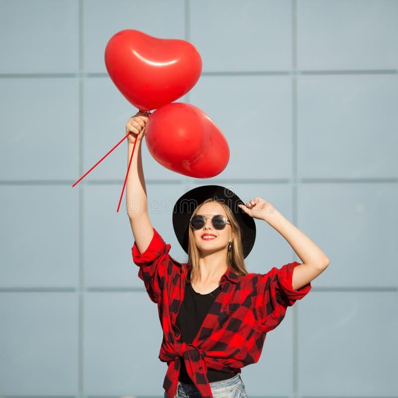 Une femme avec des verres noirs et un chapeau tient les boules rouges photographie stock libre de droits