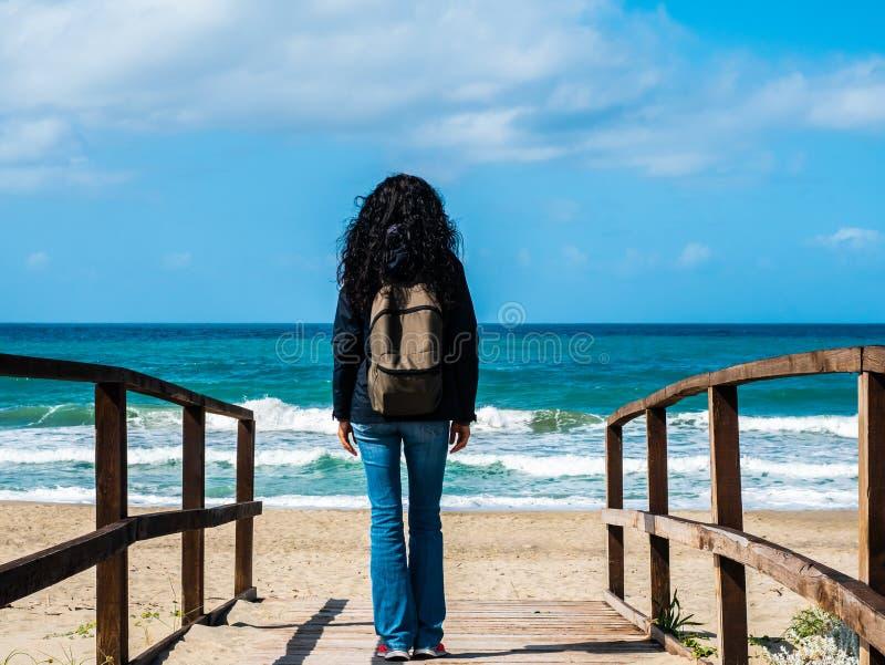 Une femme avec les cheveux noirs pris par derrière avec un sac à dos de touristes, marchant vers la plage sur un chemin en bois,  photos stock